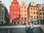 Woman tourist in Stockholm city Gamla Stan traveling lifestyle girl using smartphone blogging Europe trip vacations