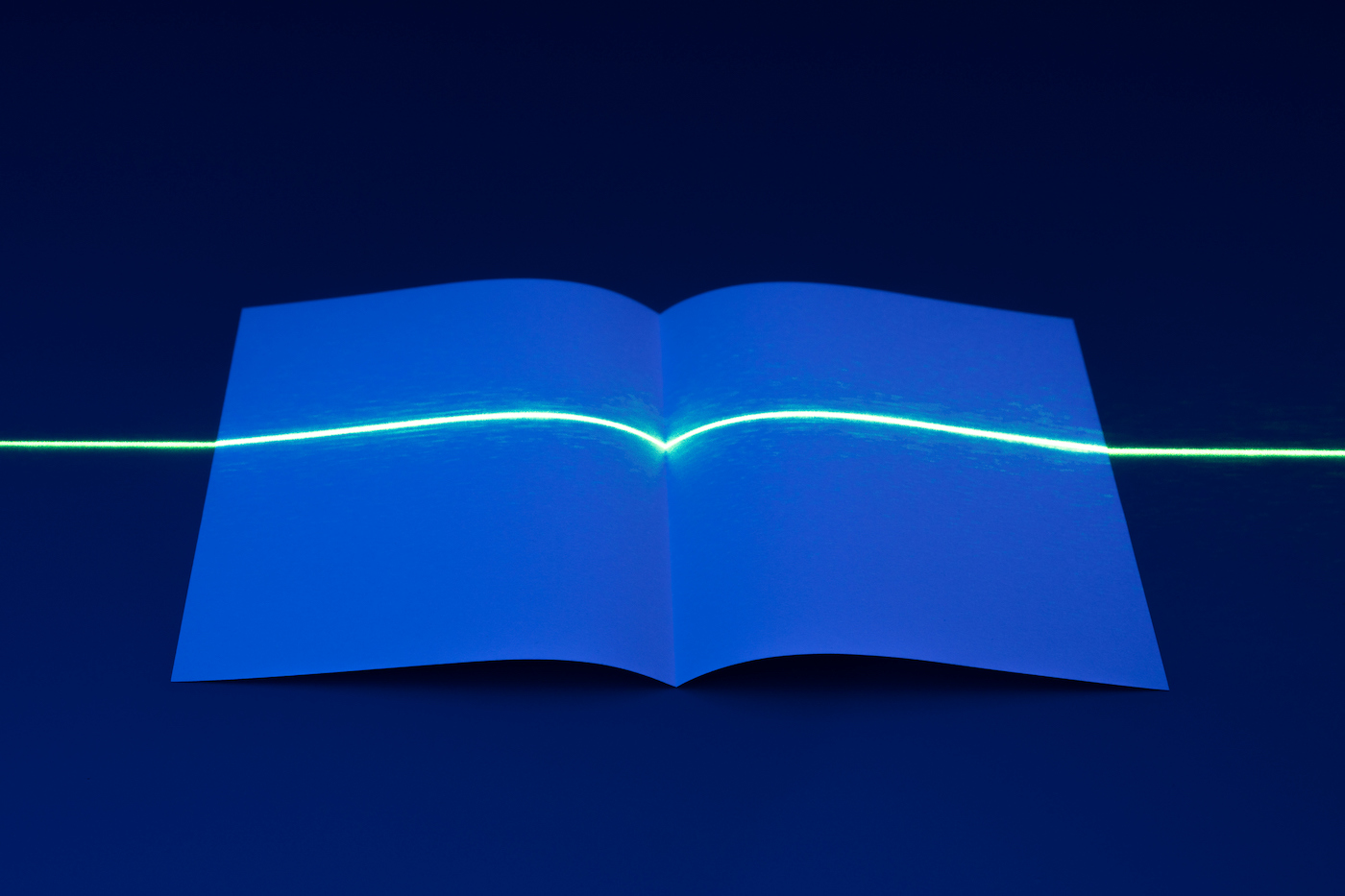 Laser Light Interrupted by Unfolded Book Shape of Paper.