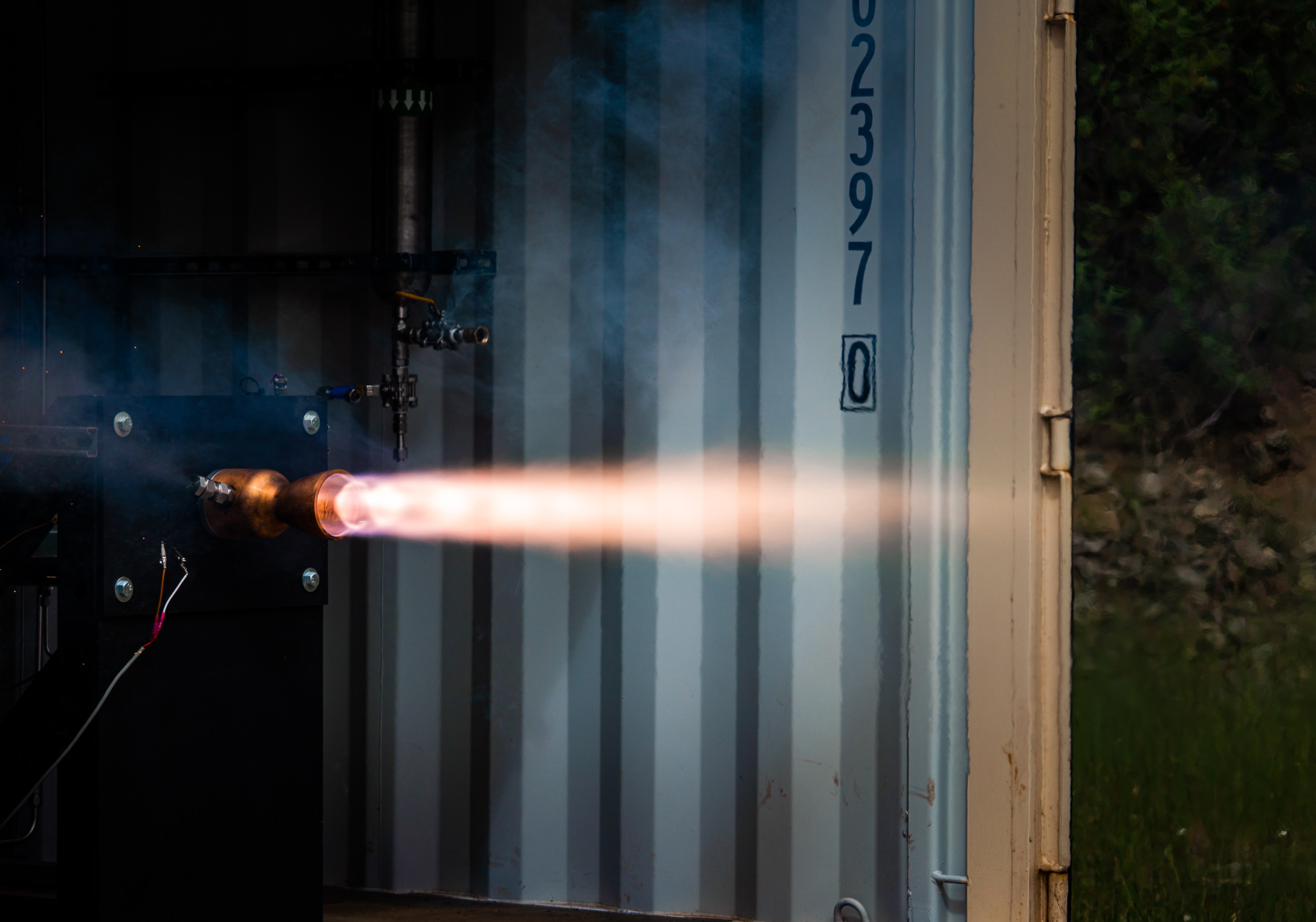 A rocket does a test fire in an industrial environment.
