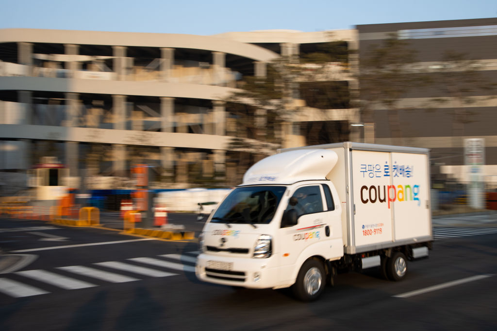 A Coupang Corp delivery truck passes the company's fulfillment center in Bocheon, South Korea, on Friday, February 19, 2021. South Korean e-commerce giant Coupang has filed for an initial public offering in the United States, and this could raise billions of dollars to fight competitors and start a year. Standard for initial public offerings in the Asian country.  Photographer: SeongJoon Cho / Bloomberg via Getty Images