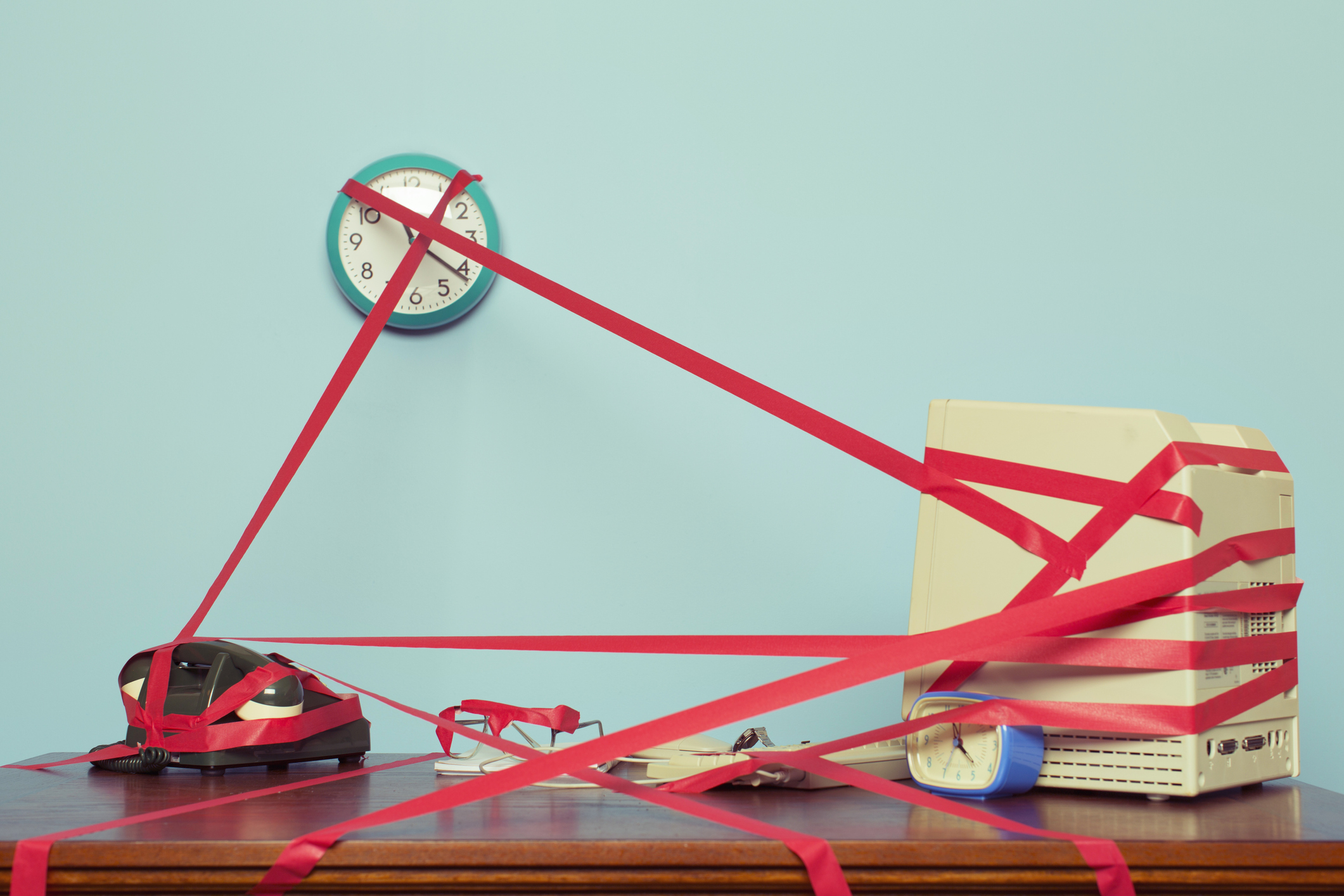 Image of a computer, phone and clock on a desk tied in red tape.