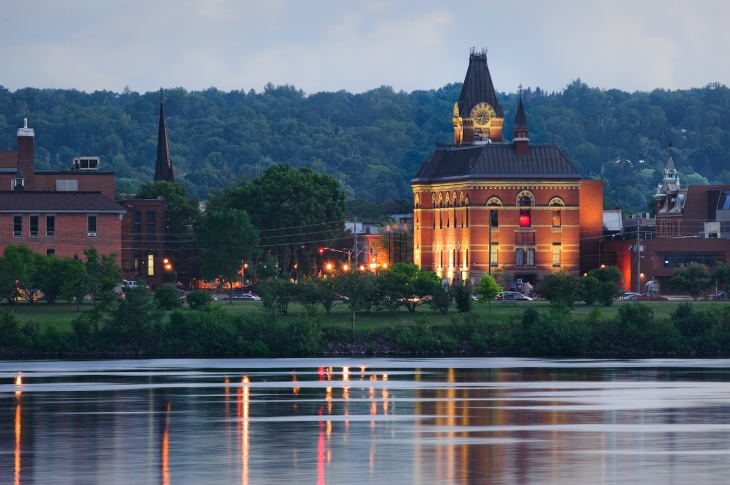 City hall reflected in the Saint John River in downtown Fredericton, New Brunswick, Canada