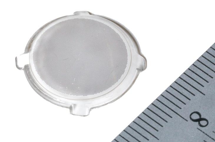 Контактная линза с множеством крошечных фотоэлектрических точек рядом с линейкой, показывающая, что она меньше сантиметра в ширину.