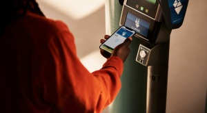 Someone using an iPhone to pay for transit at a Clipper card reader