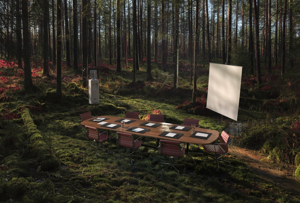 Image of an empty conference table in the middle of the forest.