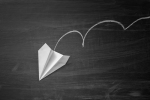 Image of a paper plane in freefall against a black backdrop.