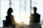 Defocussed shot of two silhouetted businesspeople having a meeting in the boardroom