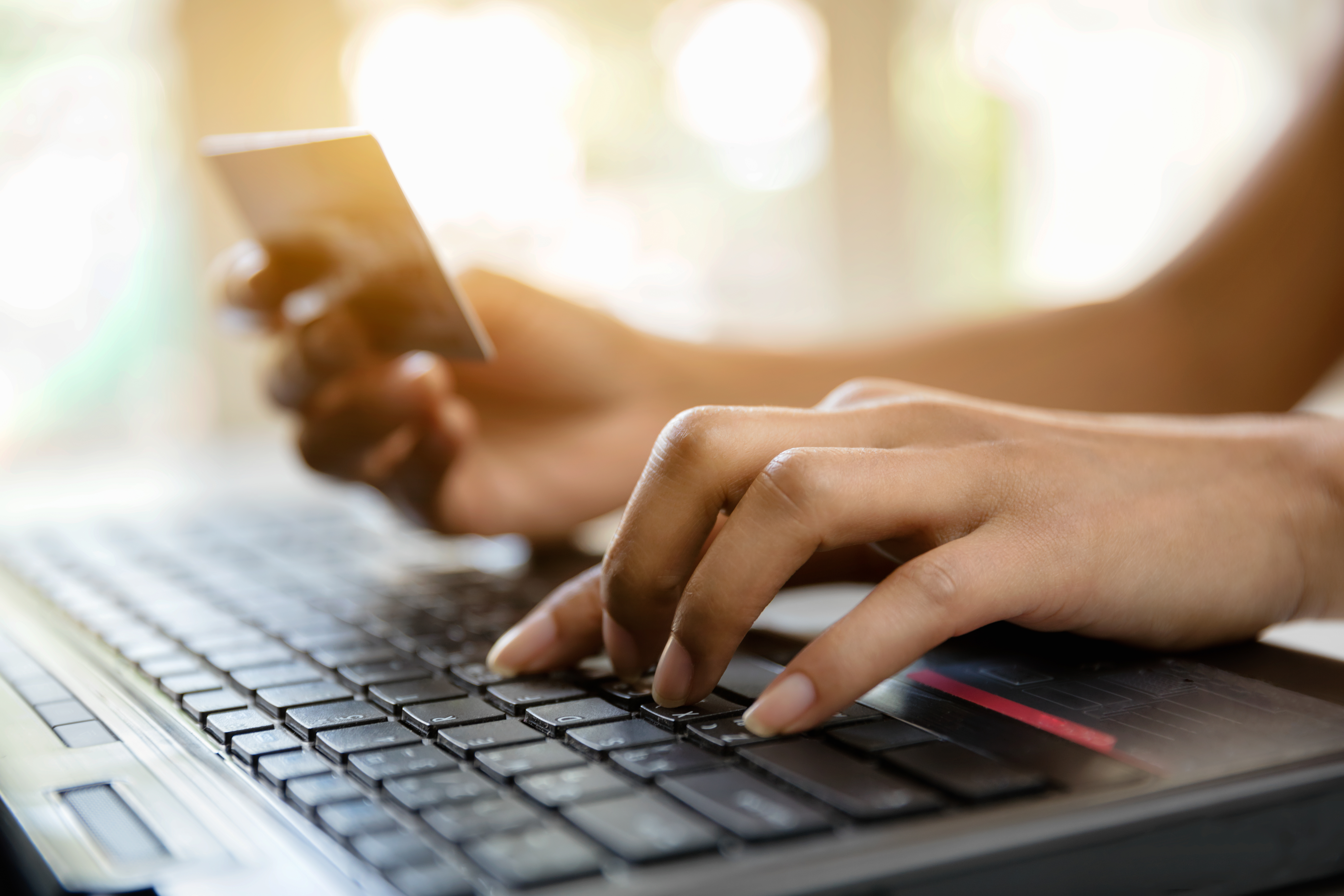 Image of hands holding credit card and using laptop to represent online shopping/e-commerce.
