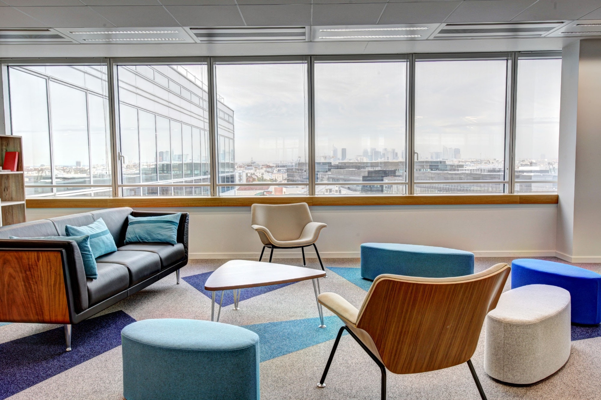 empty chairs arrayed around a modern coffee table in a vacant conference room with a city view through windows in the background