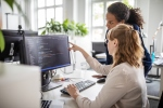 Businesswoman discussing computer program with female colleague at desk in creative office