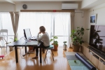 A woman using a computer in the living room of her home