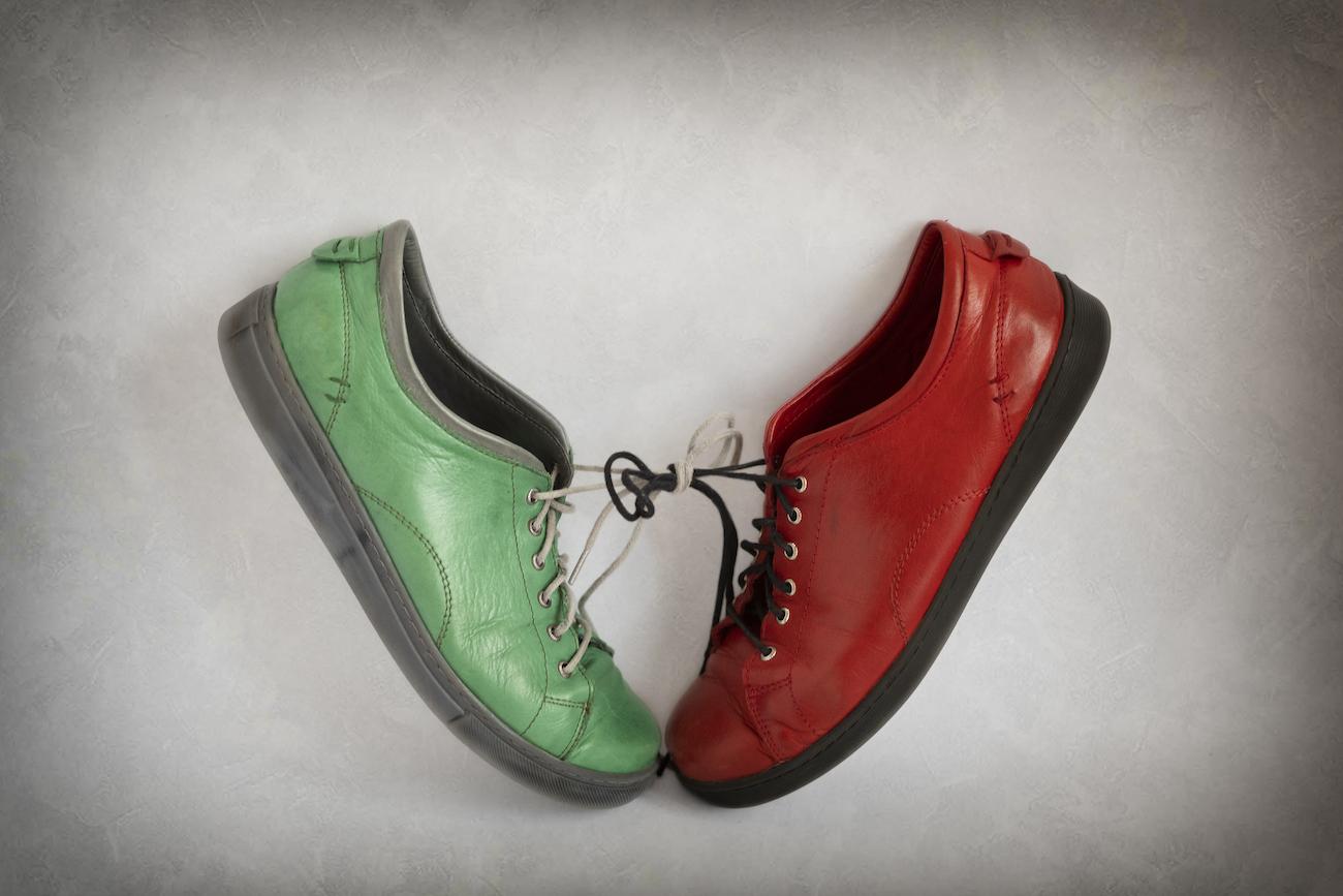 लाल और हरे रंग का जूता एक साथ बंधा हुआ