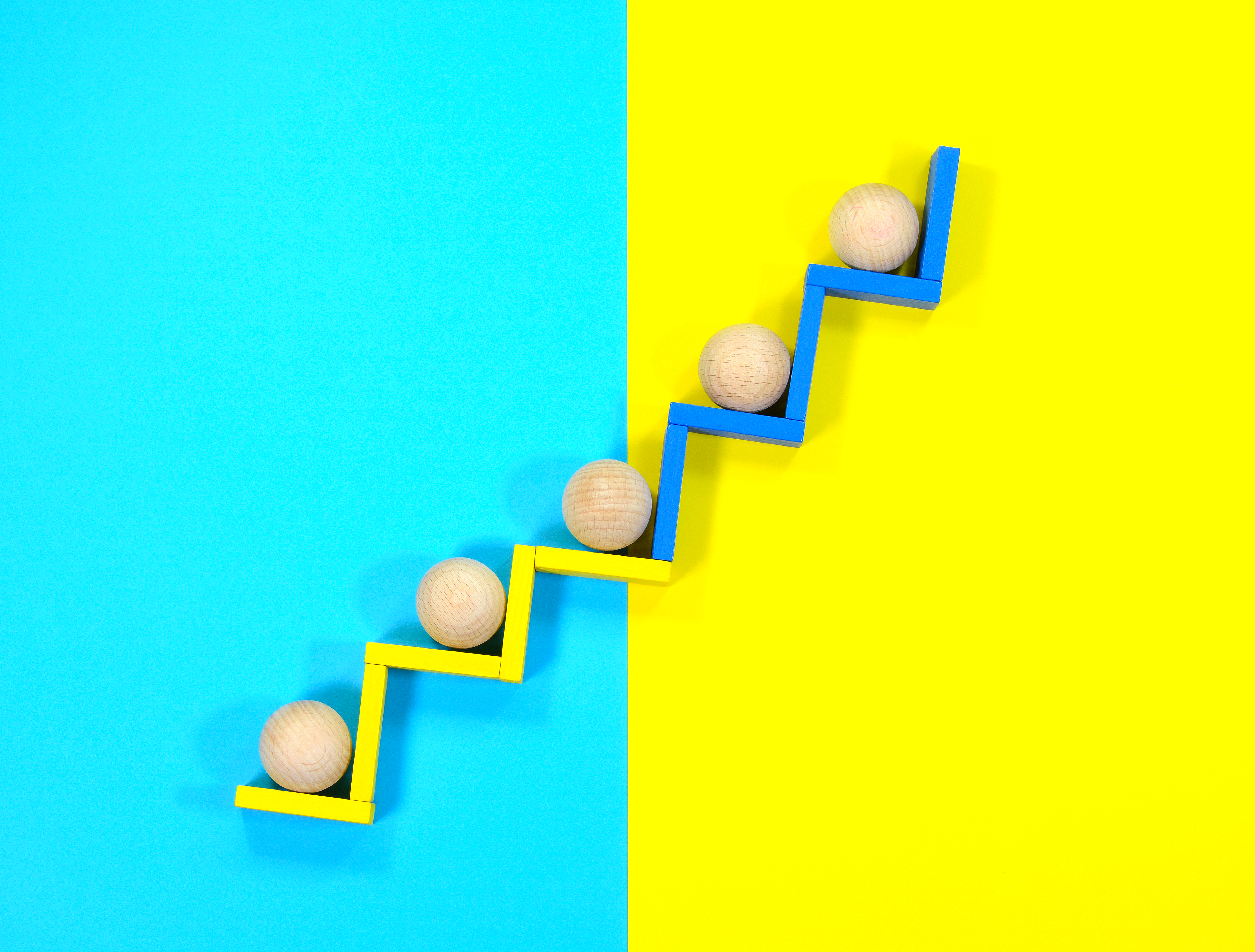 Image of five round wooden balls moving up steps to represent growth.