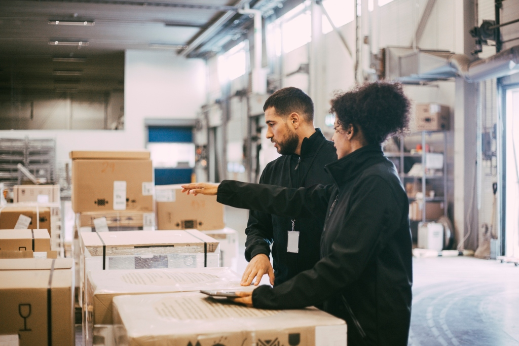 Man and woman in warehouse packing boxes.
