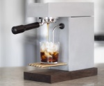 An Osma machine making coffee in a glass filled with ice.