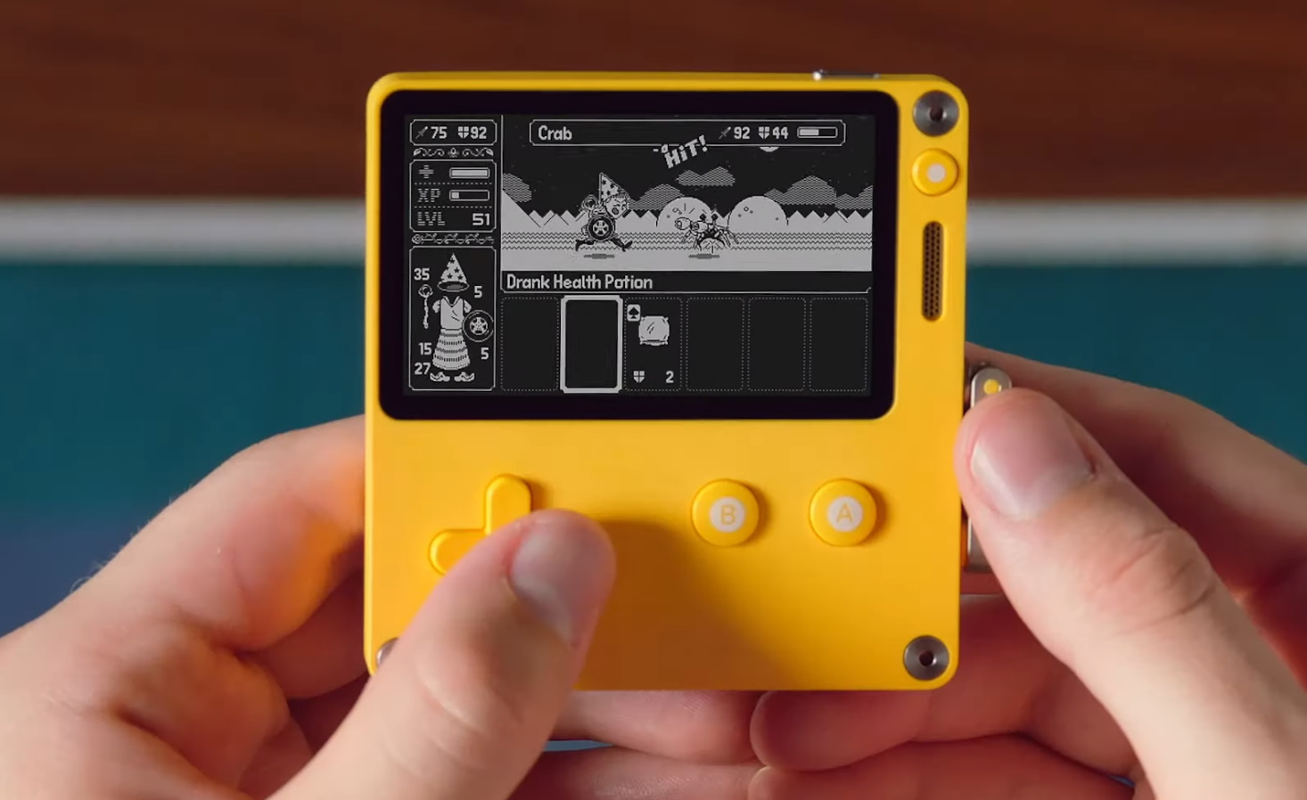 The Playdate handheld with a person playing a game on it.