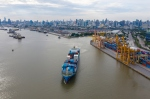 A photo of a container freight ship leaving a port in Thailand