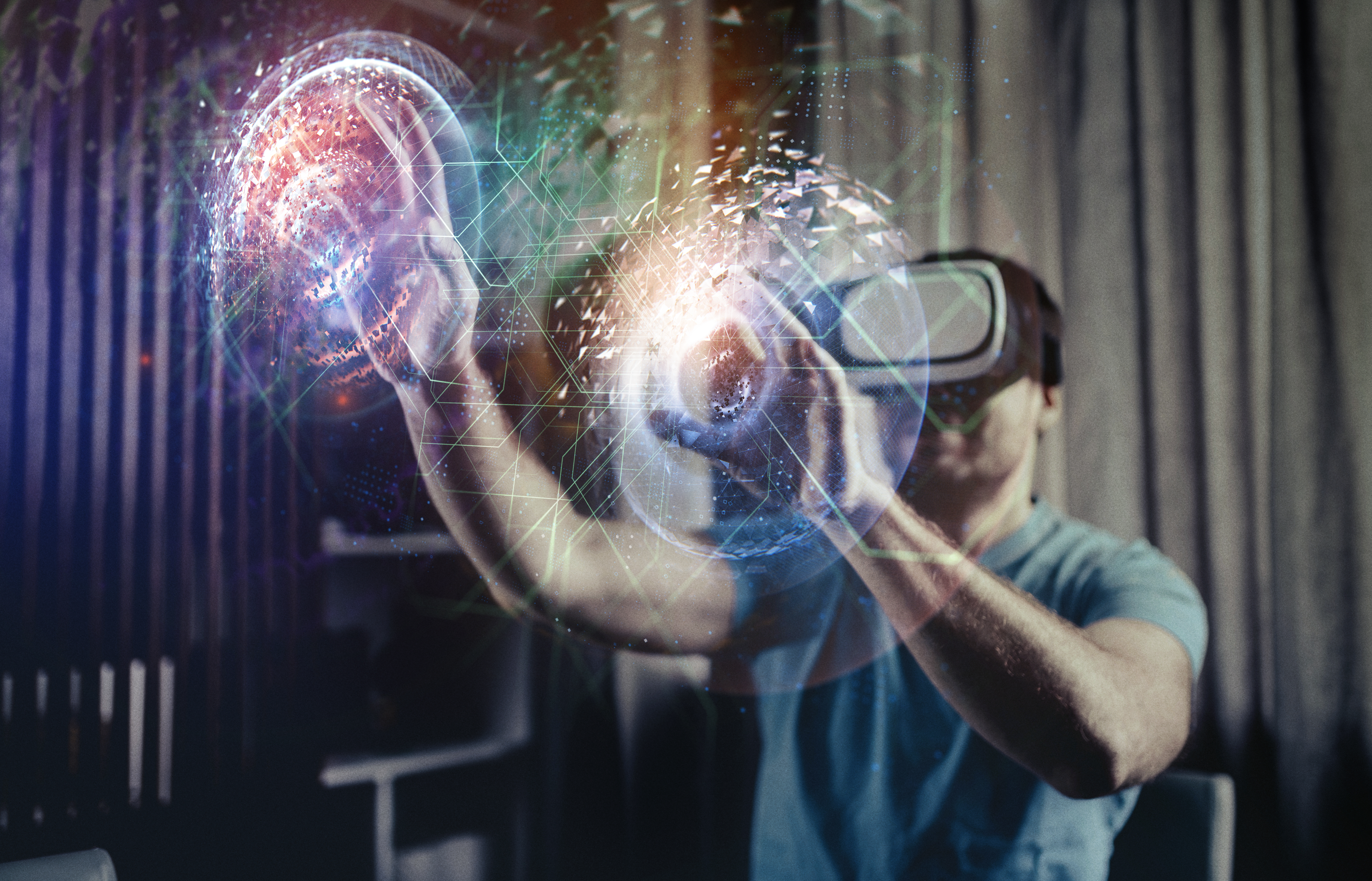 Image of a person wearing a VR headset and two 3D orbs in front of his hands.