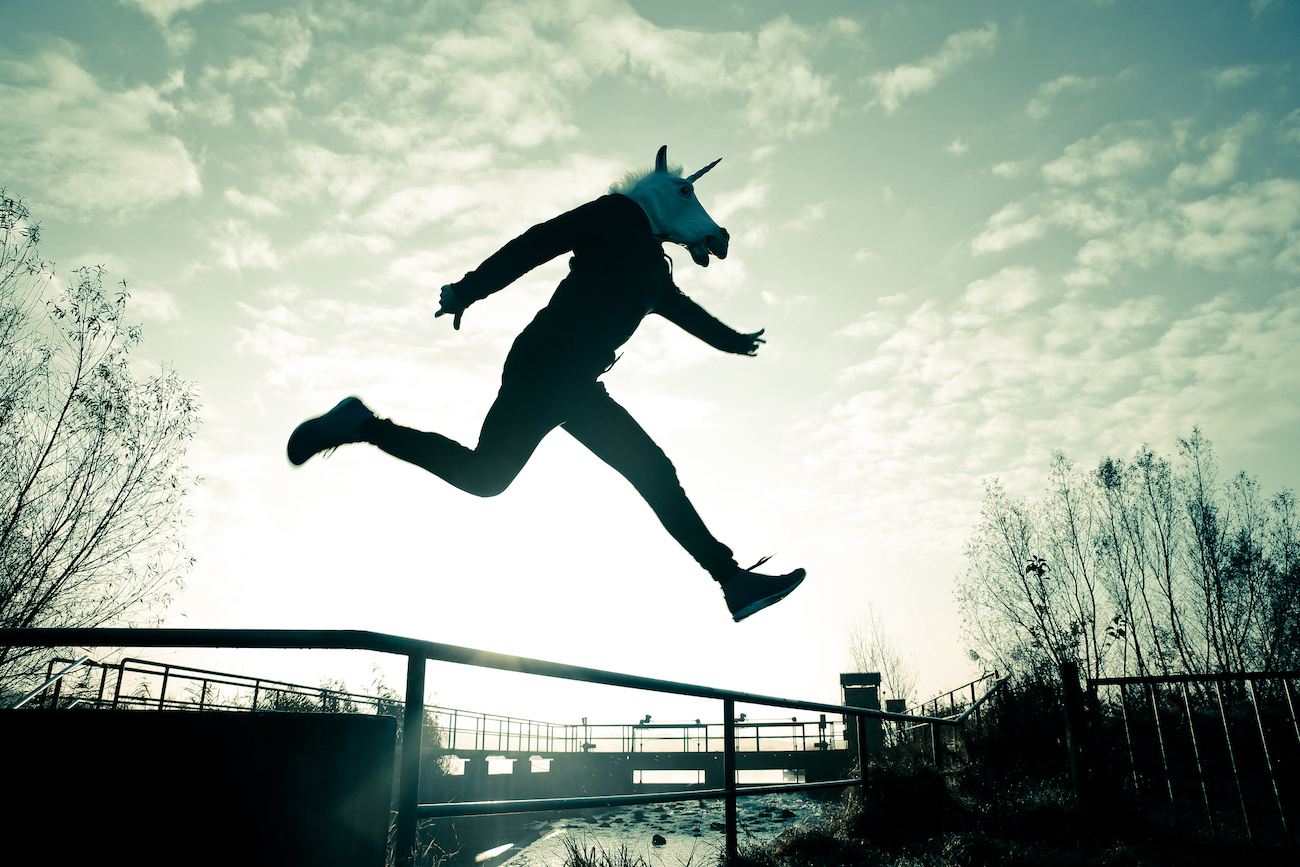 An adult wearing a unicorn mask leaps over a chain-link fence