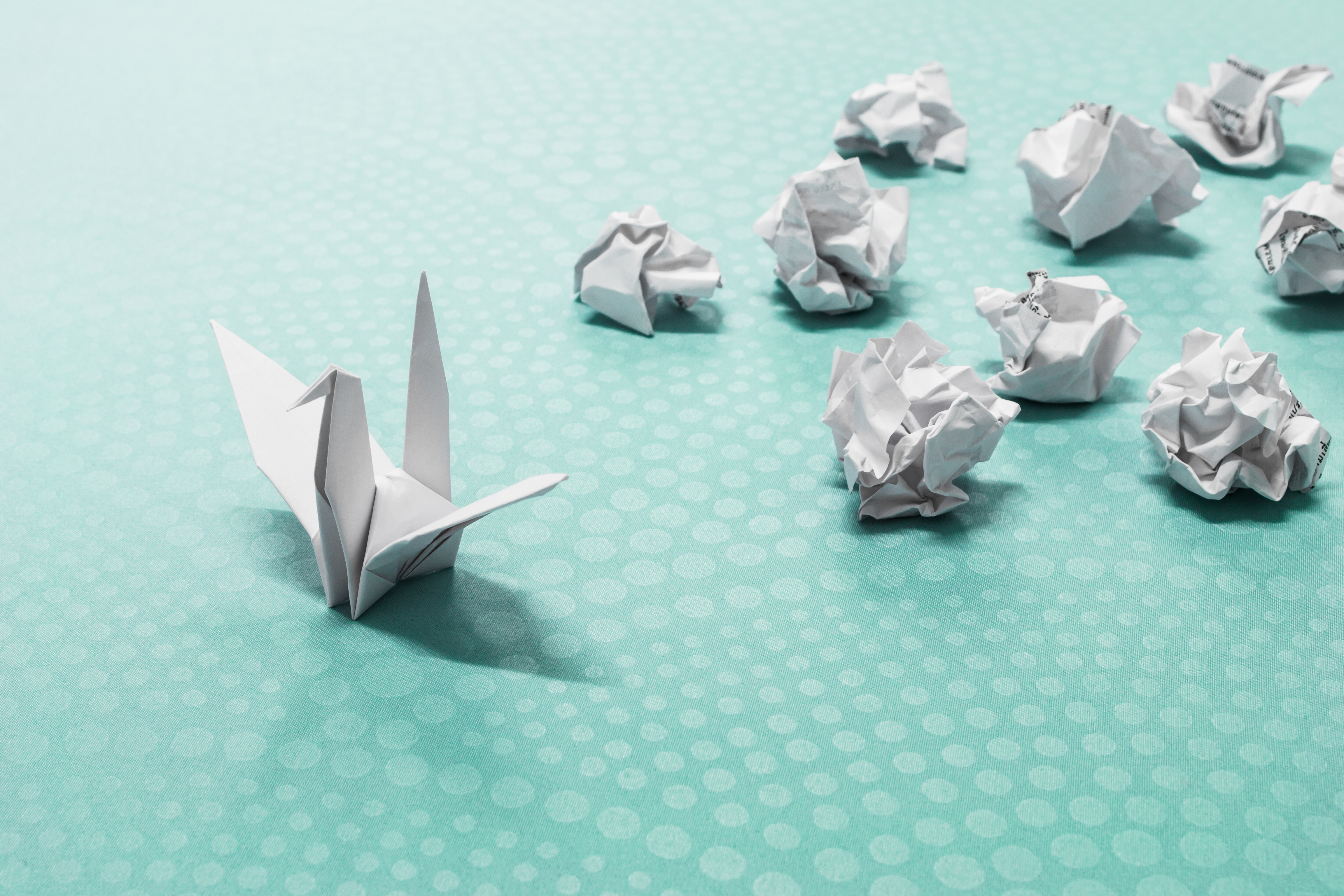 Image of an origami crane and several crumpled pieces of paper to represent success from failure.