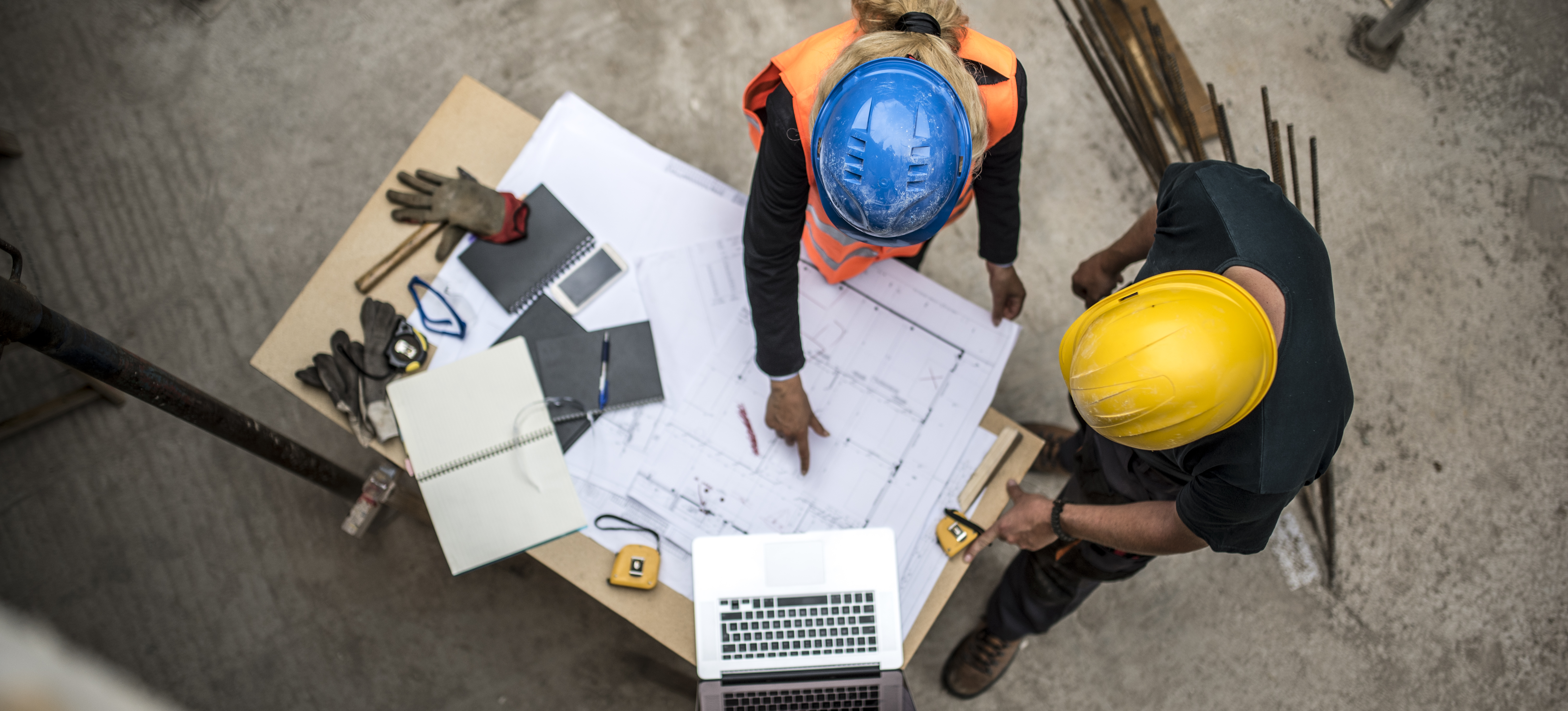 Image of two construction workers examining blueprints next to a laptop to represent tech on construction sites.