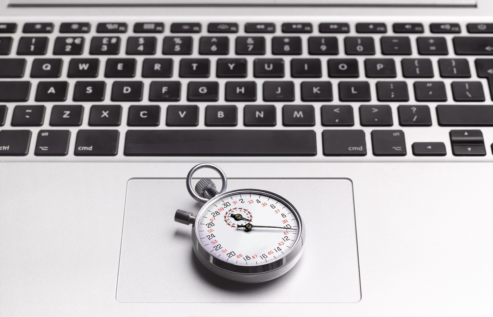 Close up of a stopwatch resting on a laptop's trackpad.