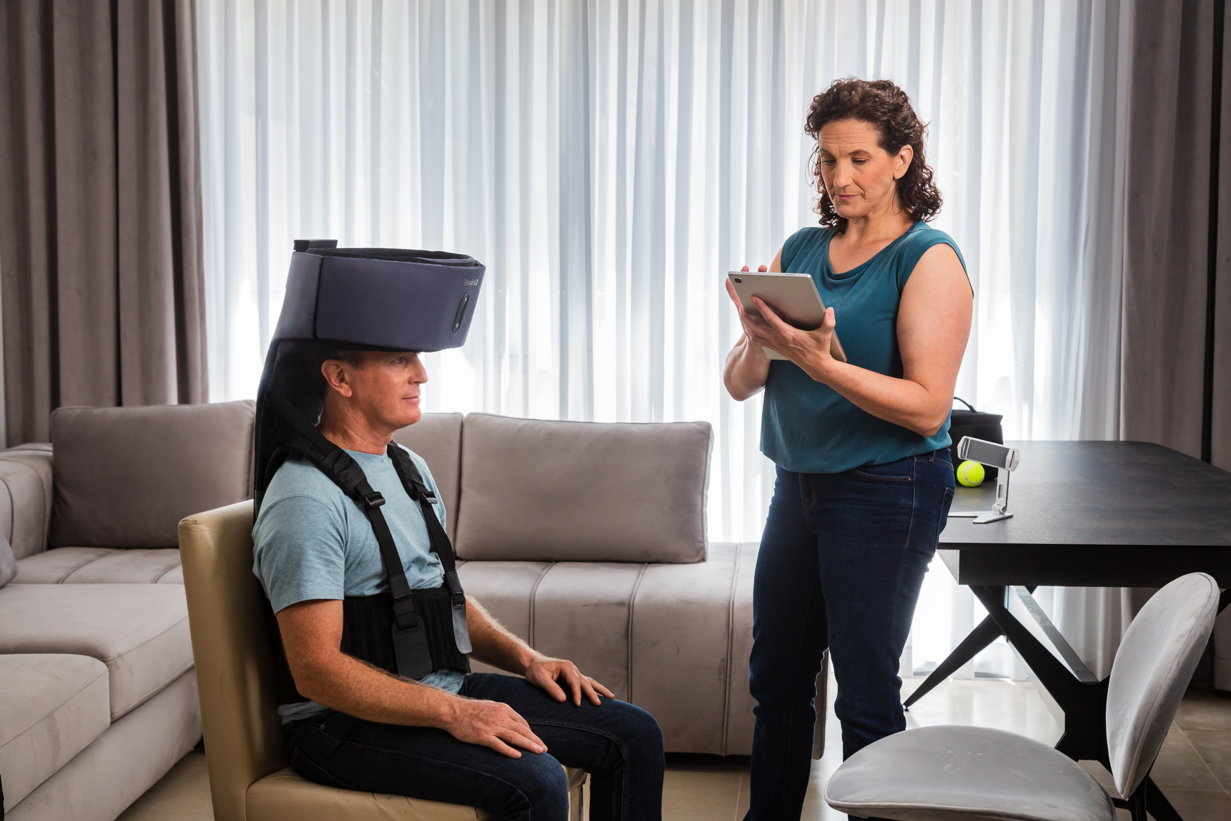 A man wears a BrainQ headset while sitting in a chair, while a woman operates a tablet near him.
