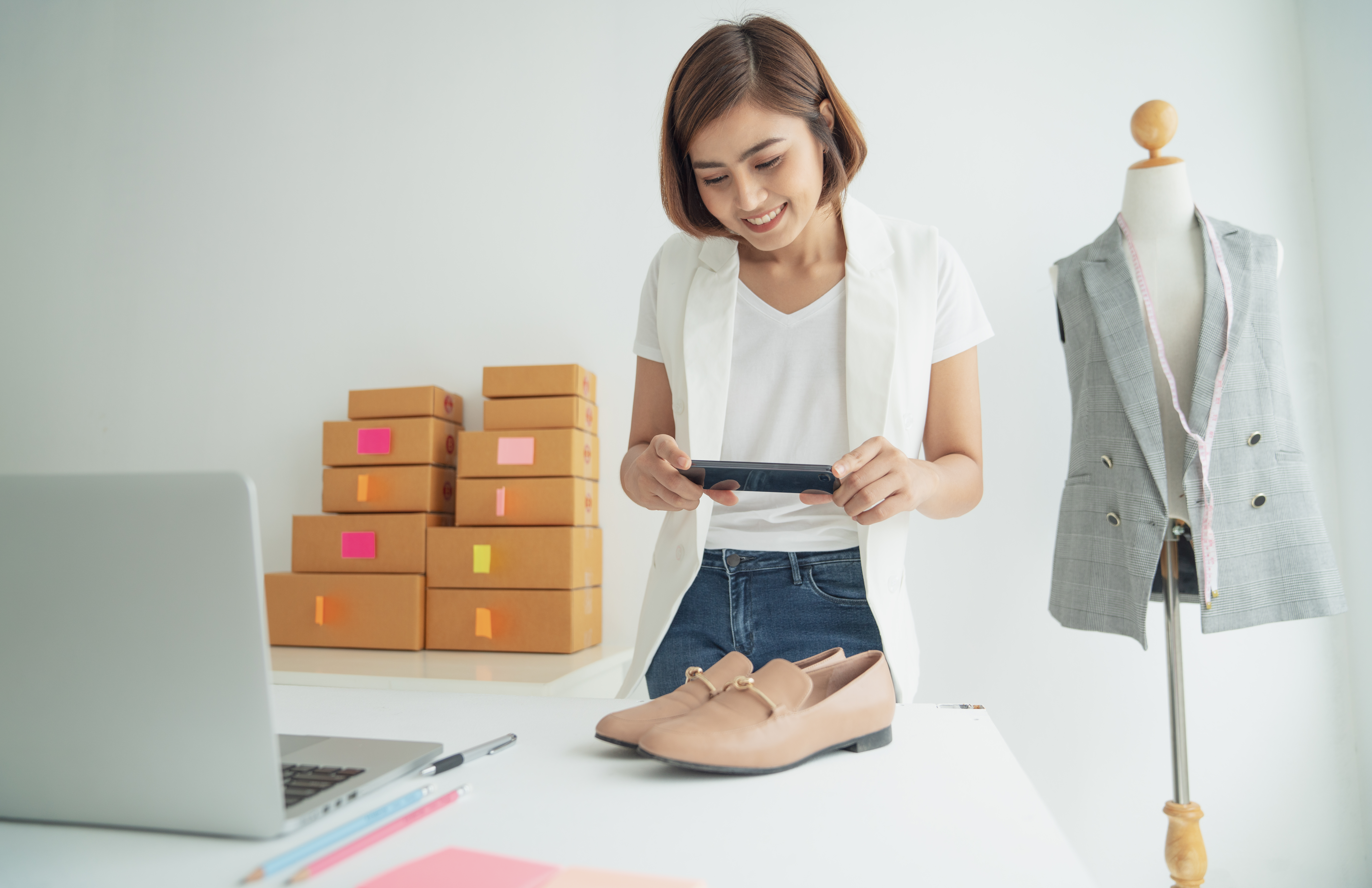 Image of a shop owner taking a photograph of a pair of shoes before mailing to represent how small businesses can compete with Amazon.