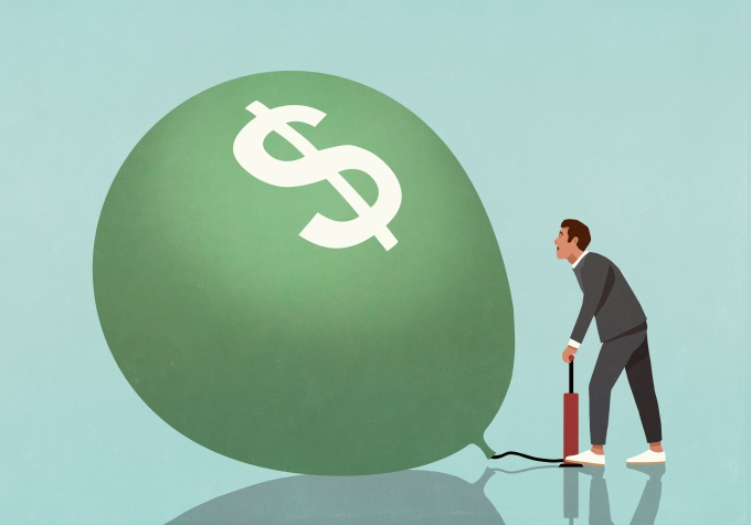Image of a businessman blowing up a green balloon with a dollar sign on it to represent investment.