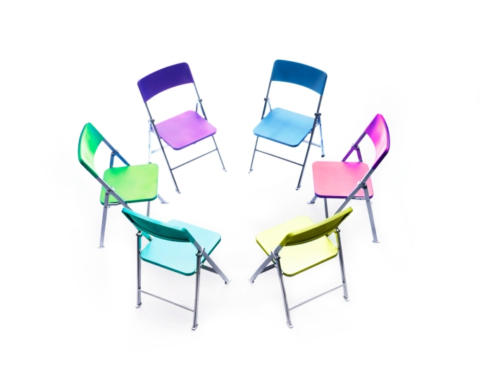 Circle of chairs of different colours.