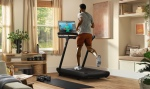 Peloton Tread, man running on the treadmill while watching workout video