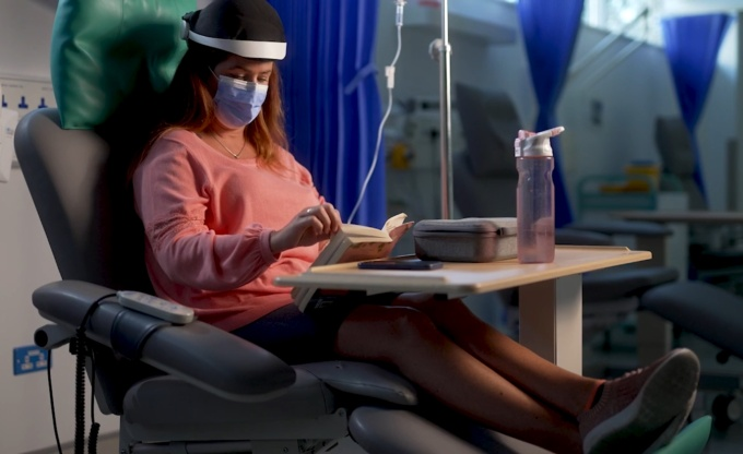 A woman sits in a chemotherapy clinic in a chair with Luminate's headset on.