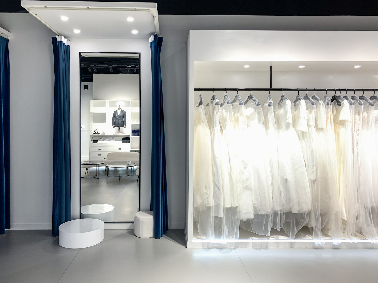 photo of a fitting room with a three-way mirror and a rack of dresses