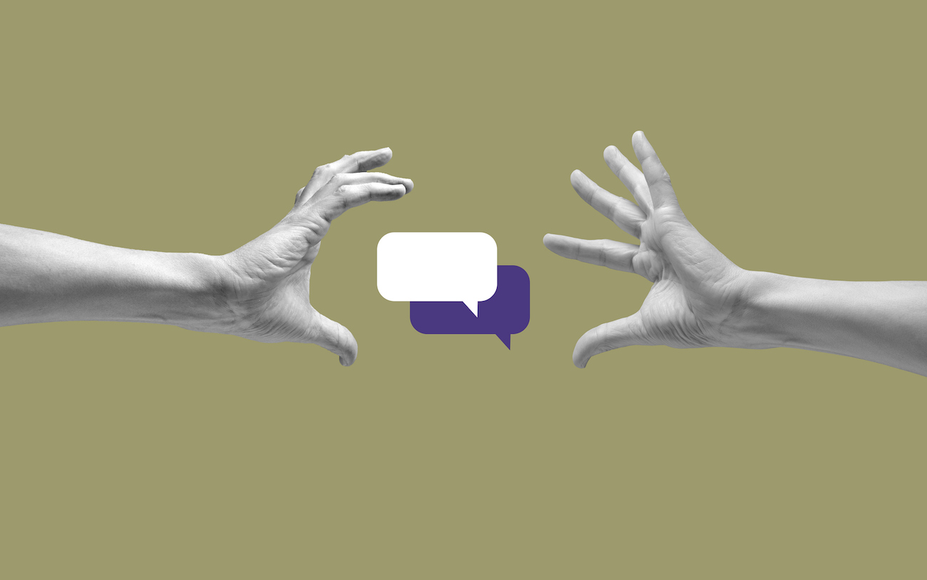Speech bubbles between two human hands against khaki background.