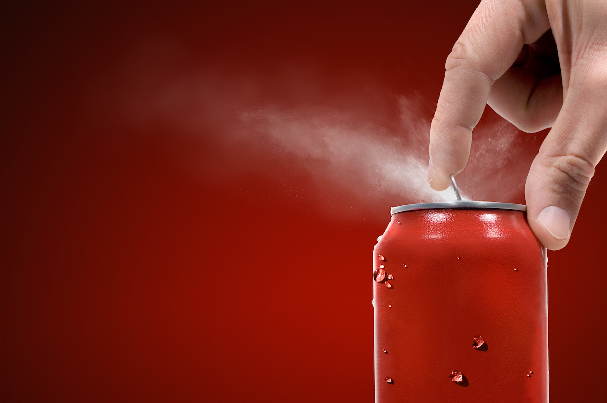 Someone pops the tab on a soda can, releasing a mist/spray