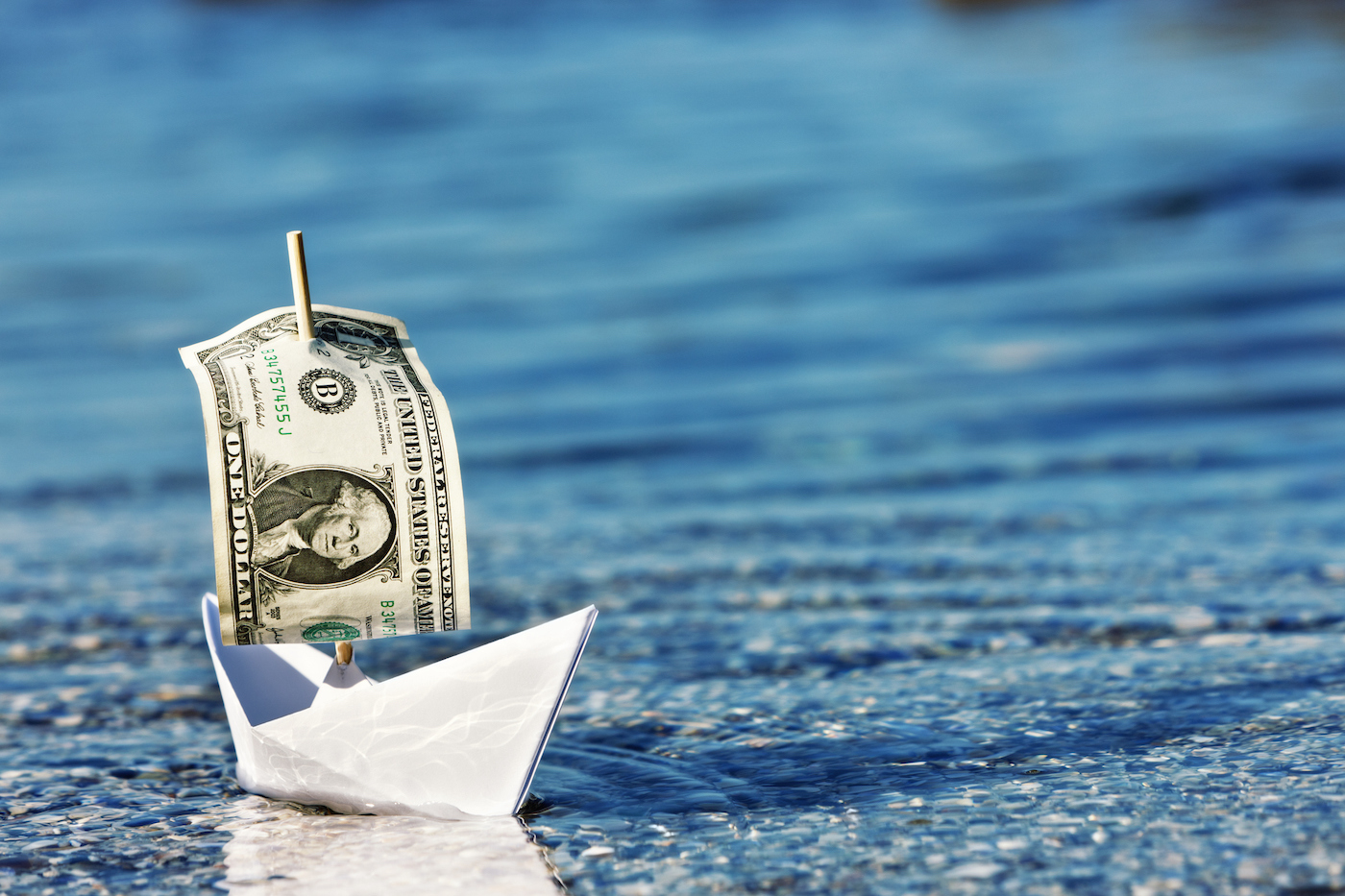 a paper boat with a dollar bill for a sail