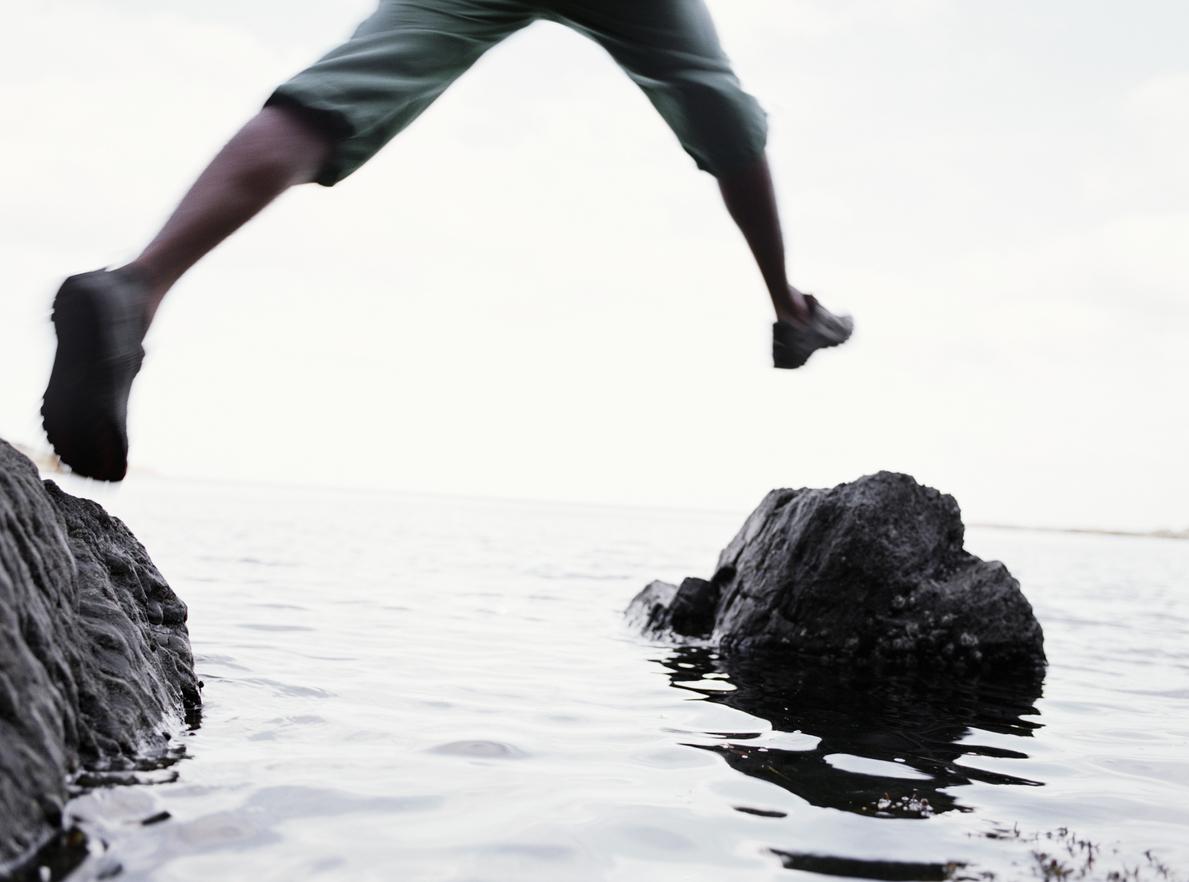 Young man jumping between rocks