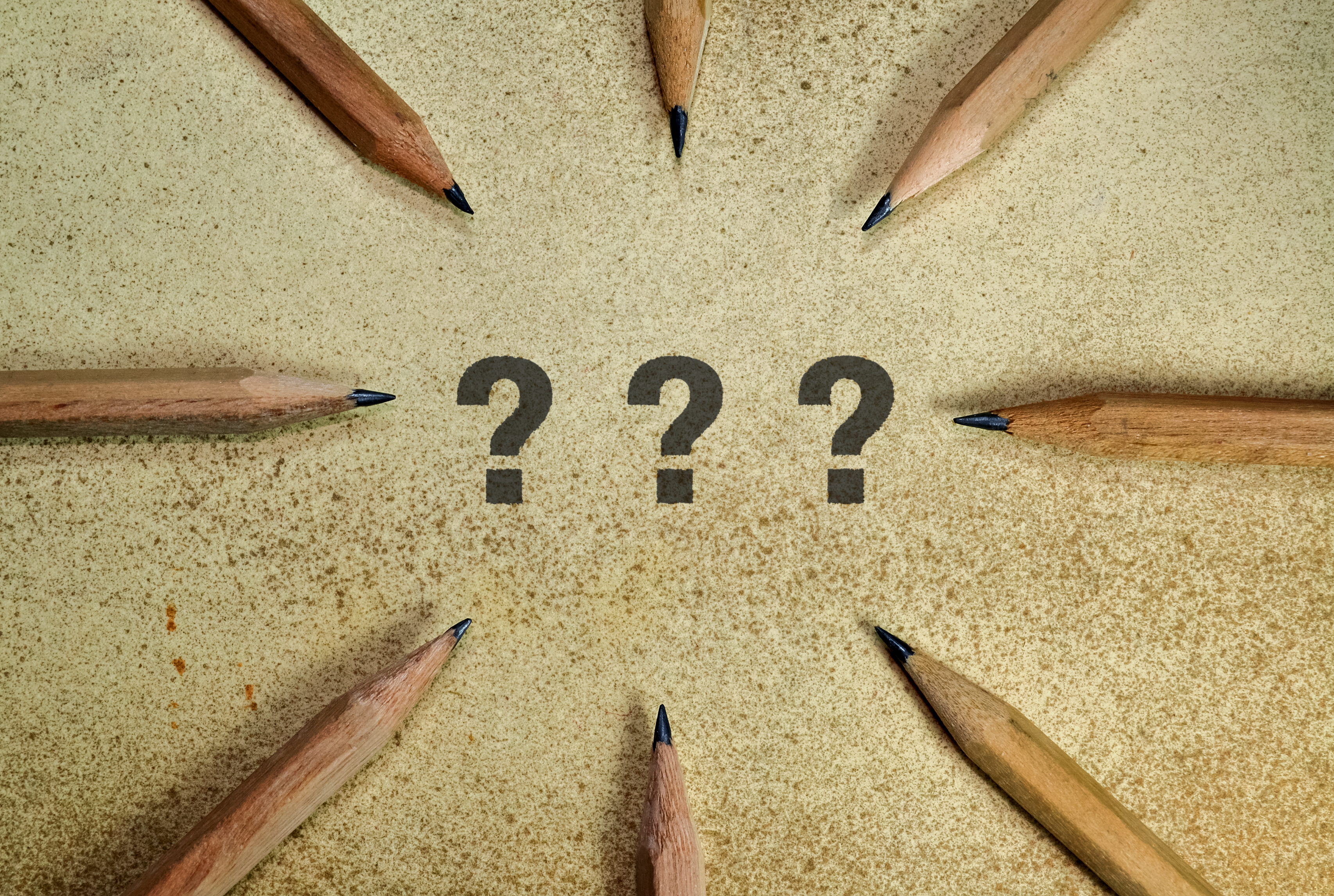 Three question marks surrounded by pencils on grunge background
