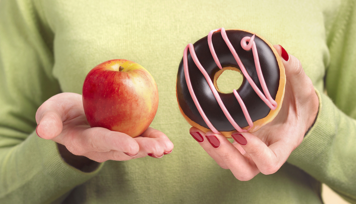 A close up of a woman's hands, one holding an apple the other hand holding a doughnut