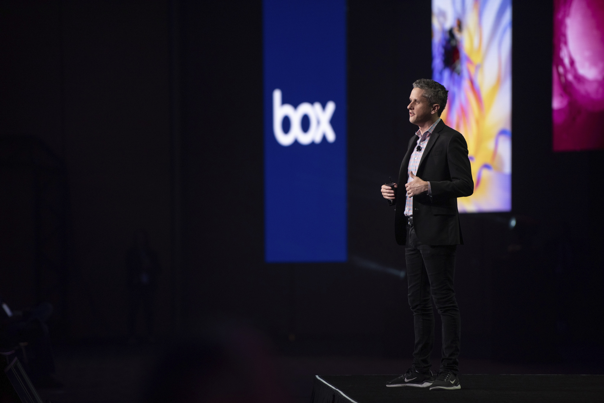 Aaron Levie CEO of Box on stage in front of Box logo.