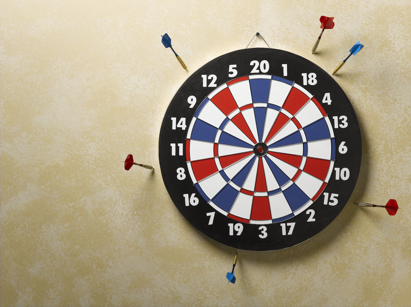 Red and blue darts in wall around red, white and blue dart board