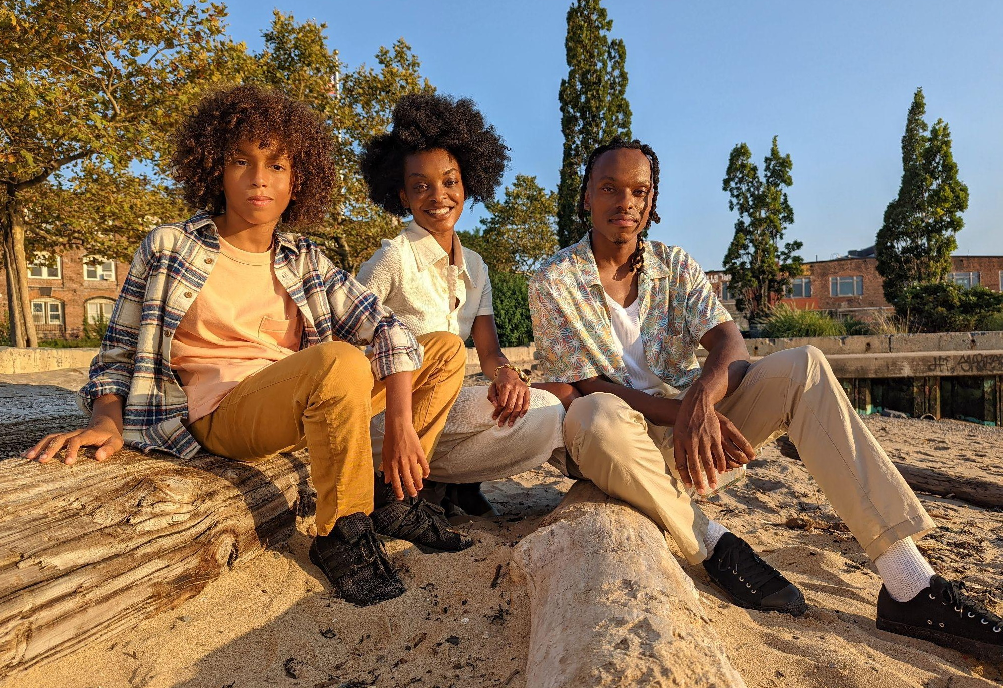 Photo of a family with dark skin sitting on the beach.
